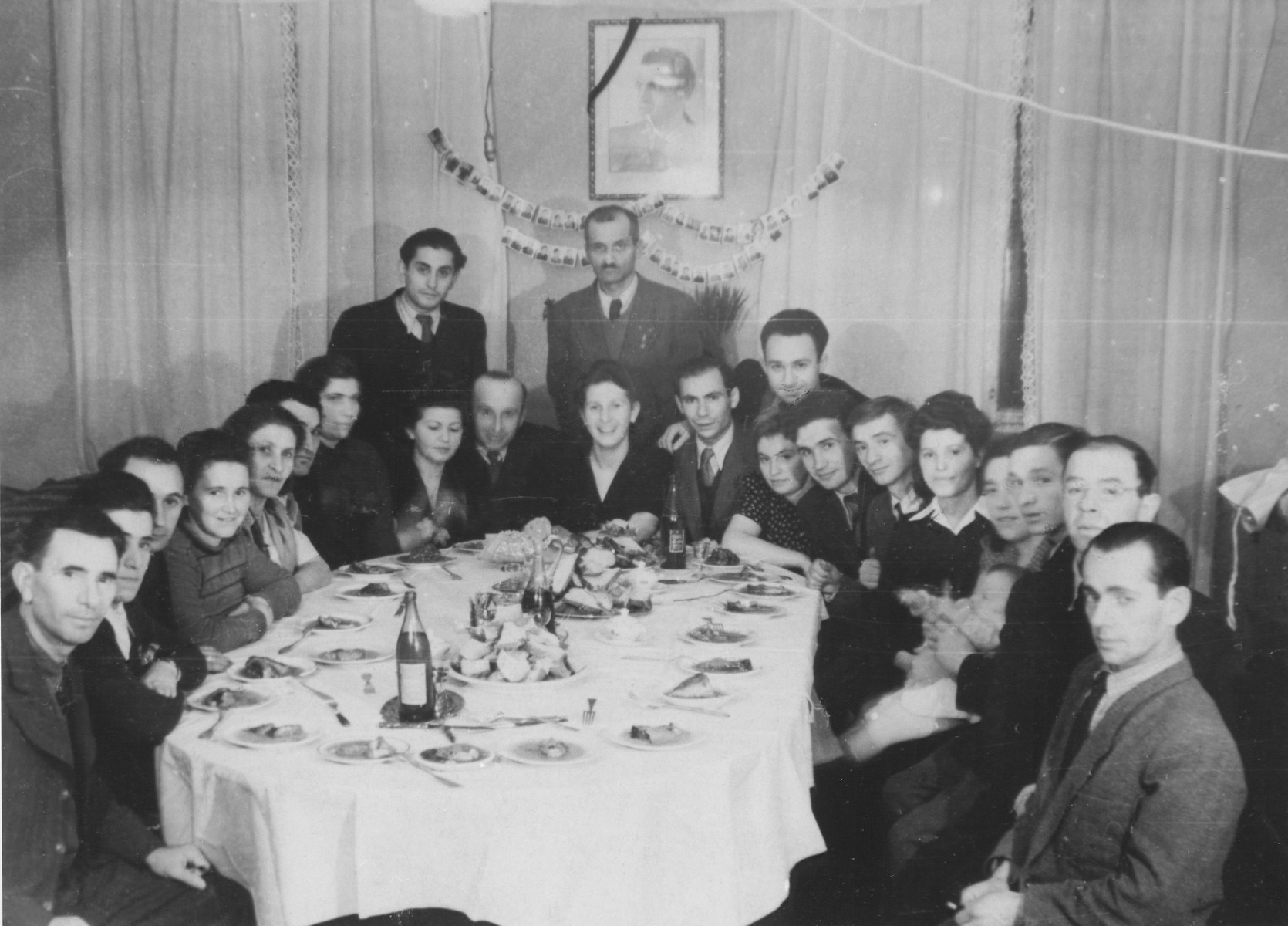 Jewish survivors from Biala Rawska at a social gathering in Lodz.  On the wall hangs two strips of ghetto ID card photos hung on ribbons.     Pictured around the table (clockwise starting from lower left) are:  (first five unknown), Idl Hamer, wife of Idl Hamer (name unknown), Zygmunt Goldberg (standing), Maria Rosenbaum (nee Koper, wife of Yumek and mother of donor), Benjamin Yumek Rosenbaum, unknown (standing), Izabella Elsztajn Sztubert (wife of Leon and aunt of donor from Skierniewce), Leon Sztubert (donor's uncle who found the collection), Salek Koper (in back), Rivka Koper (wife of Yuzek), Yuzek Koper, Jacob Koperszmidt, Mania Koperszmidt (wife of Jacob), Gitla Koperszmidt, Regina Koperszmidt (baby), Szulim Koperszmidt, Leon Koperszmidt, and unknown.  Among those pictured around the table are:  Zygmunt Goldberg (standing at the left); Maria Koper-Rozenbaum (sitting in front of Goldberg; she is the donor's mother); Benjamin Juma Rozenbaum (next to Maria on the right); Izabella Elsztajn Sztubert (next to Benjamin; she is the donor's aunt from Skierniewce); Leon Sztubert (next to Izabella; he is the donor's uncle who found the collection); Gitl Sztubert (second from the left; she is Leon's cousin).