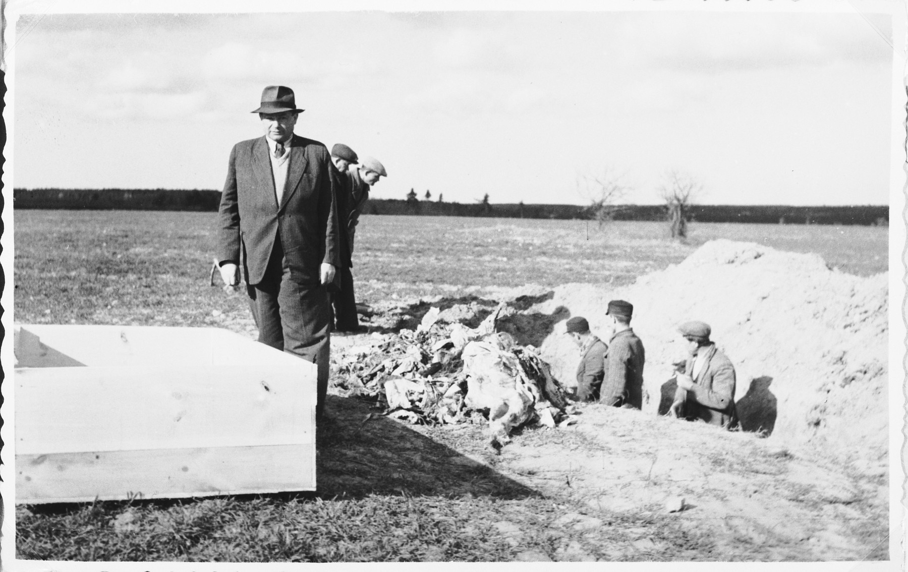 Jewish survivors and Polish workers exhume the bodies of Jews killed during the liquidation of Siemiatycze so that they can be properly reburied at the entrance to the Jewish cemetery.  Yehoshua Kejles is standing at the front.  His father, Efraim Kejles, was among those murdered.