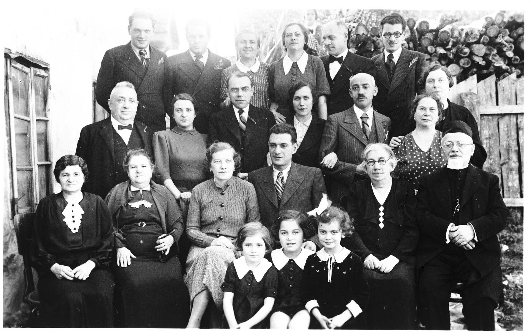 Group portrait of family members at the wedding of the Jewish couple, Silva Deutsch and Salamon Basch.  Pictured in the front row from left to right are: Vera Apler, Zdenka Apler and Edita Deutsch.  Second row: Charlotte Basch, unknown, Silva Deutsch, Salamon Basch, Katarina Deutsch and Rabbi Leopold Deutsch.  Third row: unknown, Loni Basch, Ljudevit (Ludva) Vrancic, Irma Deutsch, Erne Deutsch and unknown.  Top row: Arnold Basch, Joszi Basch, Giza Deutsch, Blanka Apler, Rudy Apler and Bernard Basch.