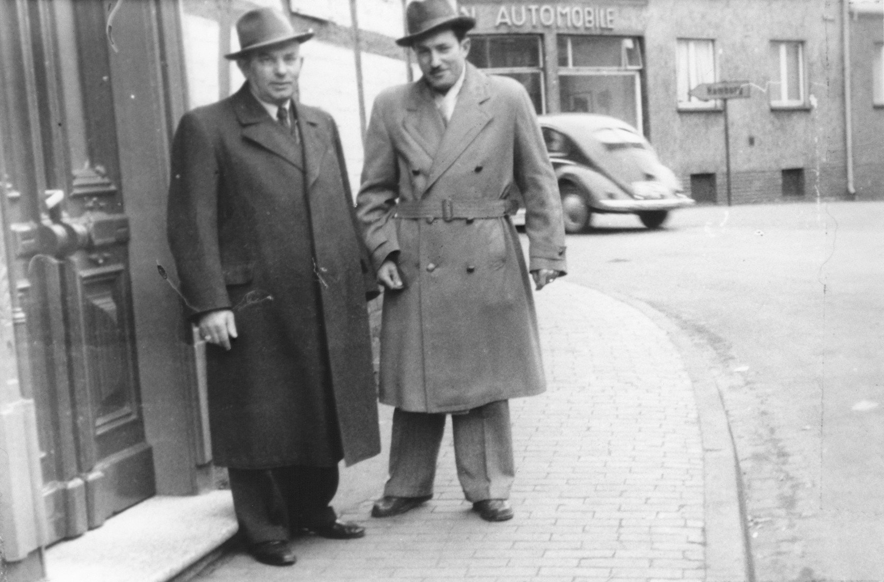 Two Jewish DPs from Oswiecim, Poland pose on a street in Celle, Germany.  Pictured are Natan Akiwa Silberger (left) and his son, Szmuel Aron (right).