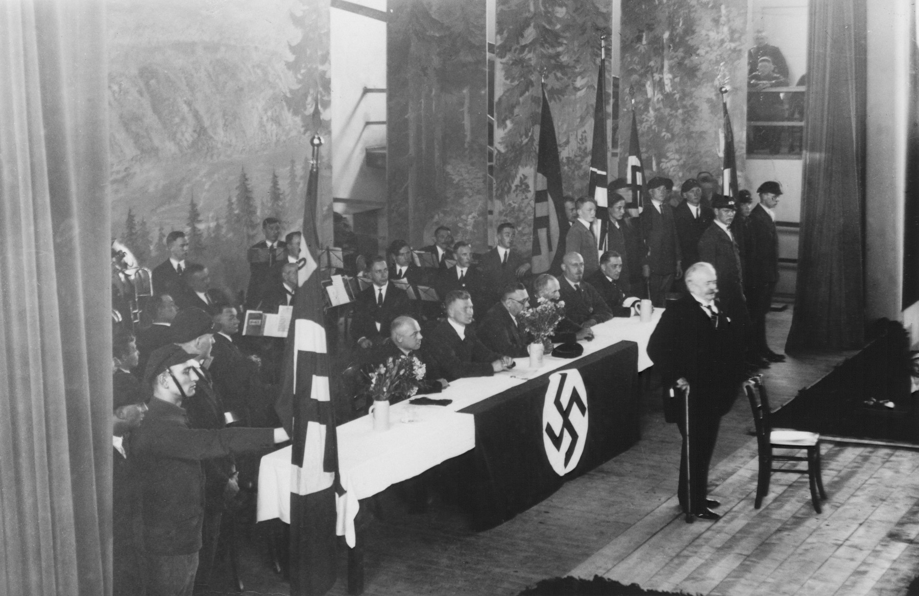 General Karl Litzmann speaks to a gathering of Nazi officials at the Stadthalle in Bad Blankenburg.  An orchestra sits behind the speakers' table.