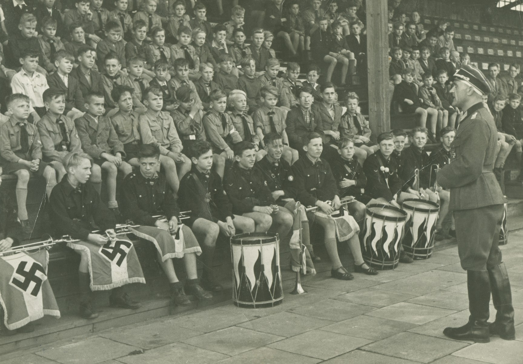 Young members of the Hitler Youth sit in a stadium behind a row of buglers and drummers.
