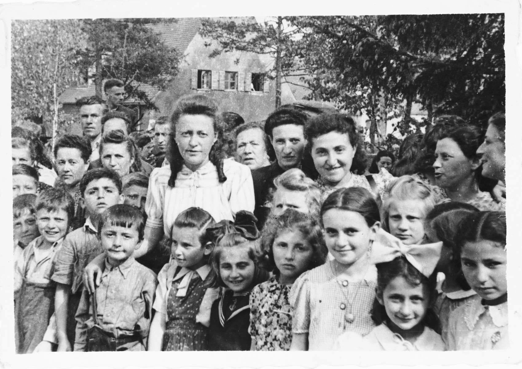 Group portrait of women and young children in the Foehrenwald DP camp.  Among those pictured is Evelyn (Yochevett) Zektzer (later Elbaum), the woman standing on the left.