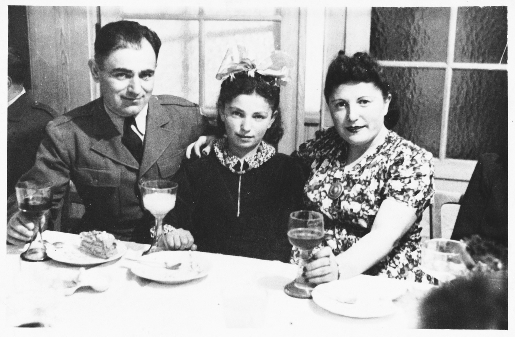 Issak, Chaia and Fira Libstug enjoy a festive meal at the Foehrenwald displaced persons camp.