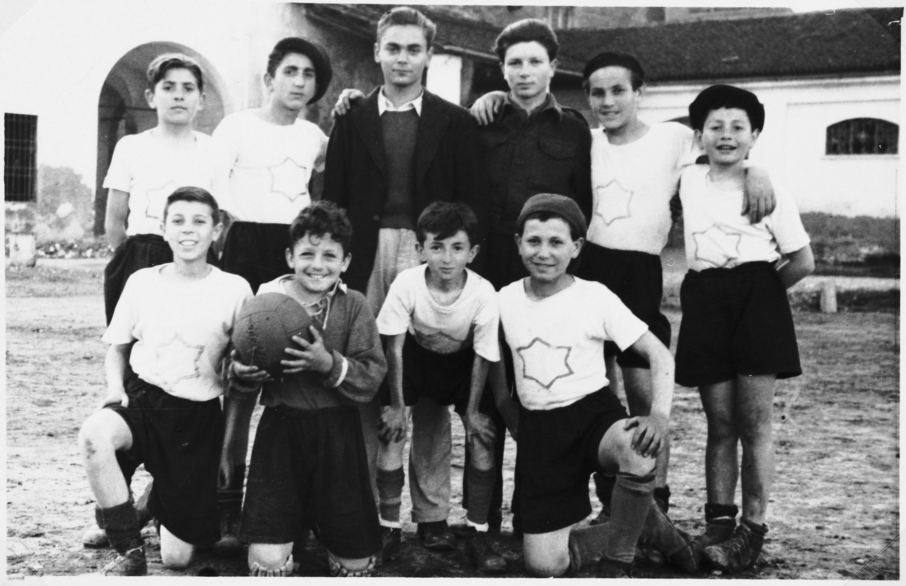 Group portrait of the members of a boy's soccer team wearing shirts with a Star of David.  Those pictured include Sam Freger (first row, second from the left), Ernst Schnittlinger (back row, center) and Shie Zoltak (back row, third from the right).