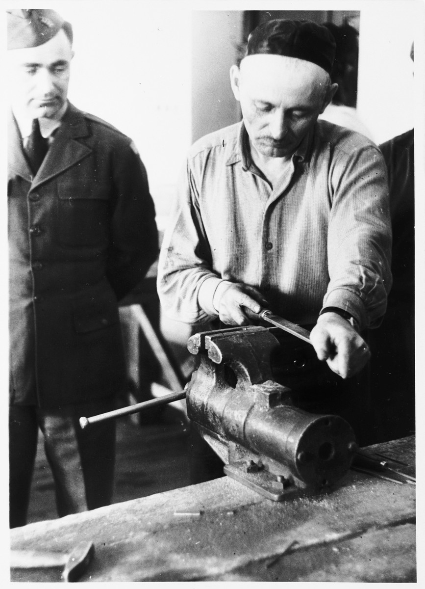 Issak Libstug, wearing his AJDC uniform, watches a religious man filing a piece of metal in a workshop in the Foehrenwald DP camp.