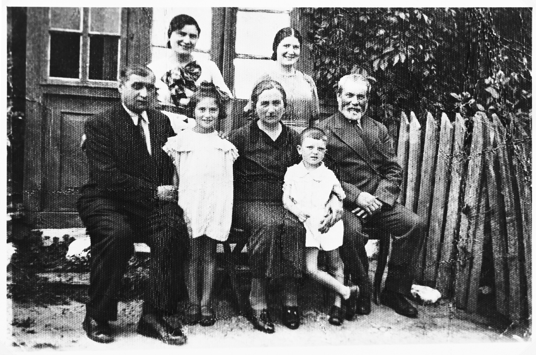 The Kejles family poses outside its home in Grodzisk.  Pictured from left to right: front row: Menashe Hirszfeld (a brother-in-law of Efraim Kejles visiting from Warsaw),Chayale Kejles (she perished in Treblinka), Riva Kejles, Shie Zoltak, and Efraim Kejles.  Back row: Rachel Kejles and Itke Kejles.