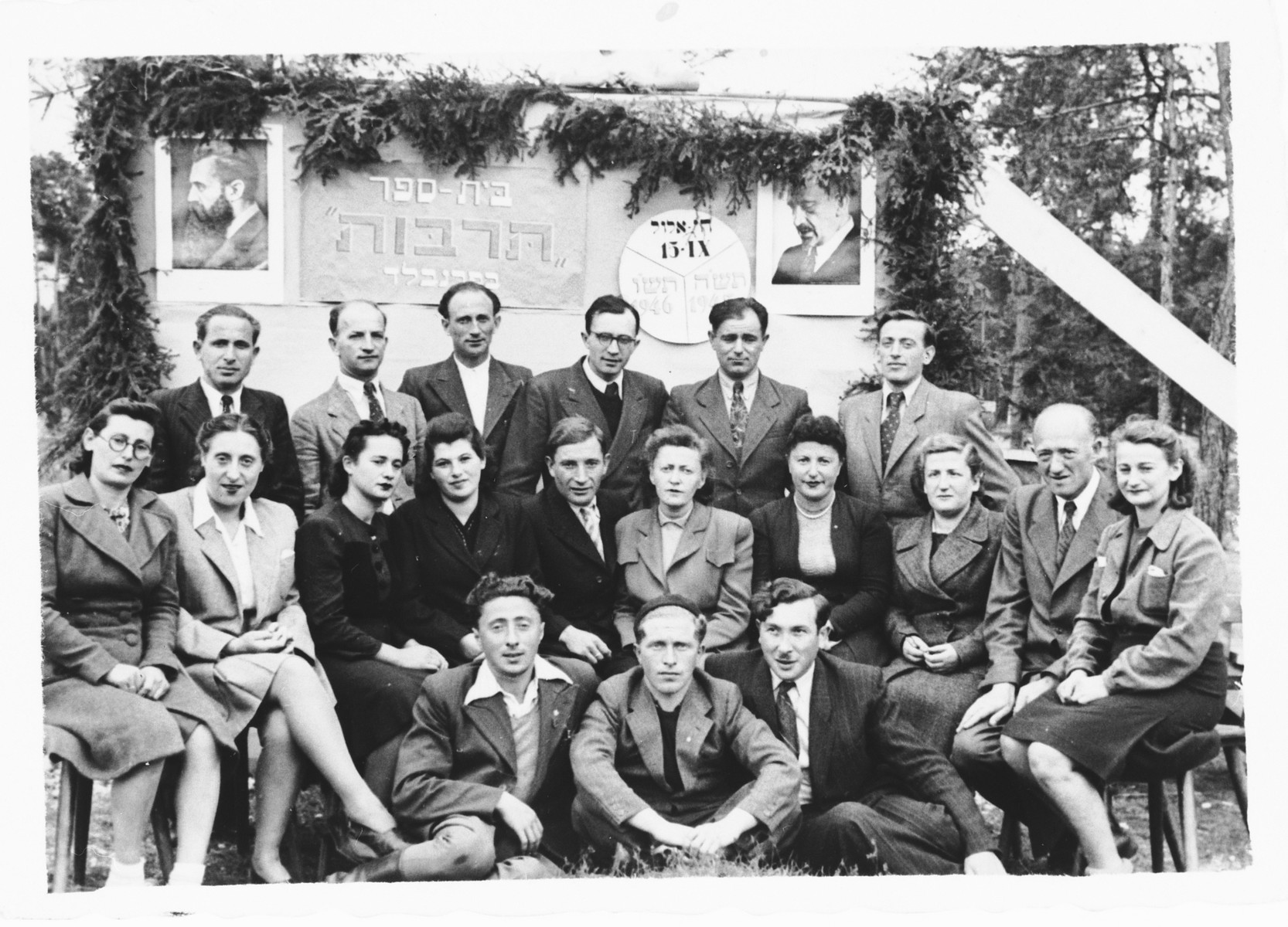 Jewish DPs gather in front of a sign celebrating the Hebrew Tarbut school in the Foehrenwald displaced persons camp.  Among those pictured is Stanley Zektzer, seated in front lower left
