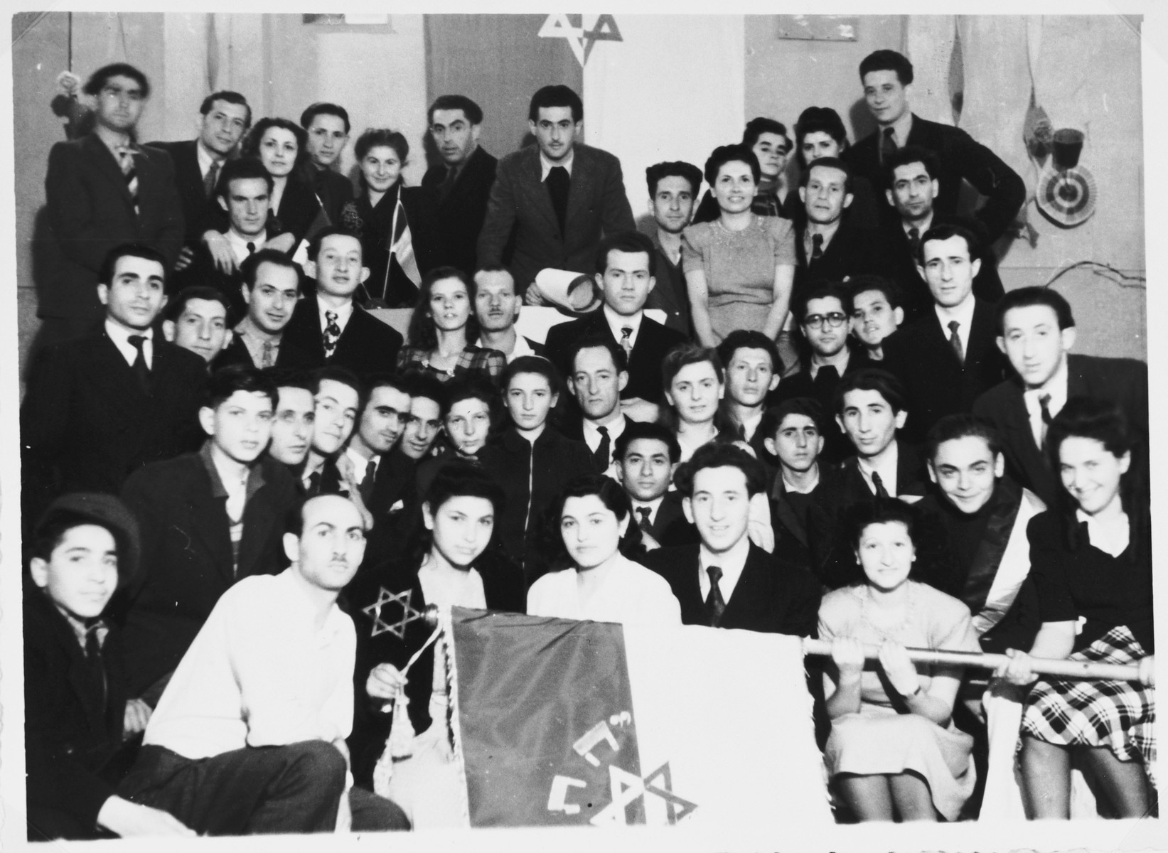A large group of Jewish DPs pose with Zionist flags in the Cremona DP camp.  Those pictured include Shie Zoltak, Nusia, Frank Kaminski, Motele Hostik and Chalina Libeskind.