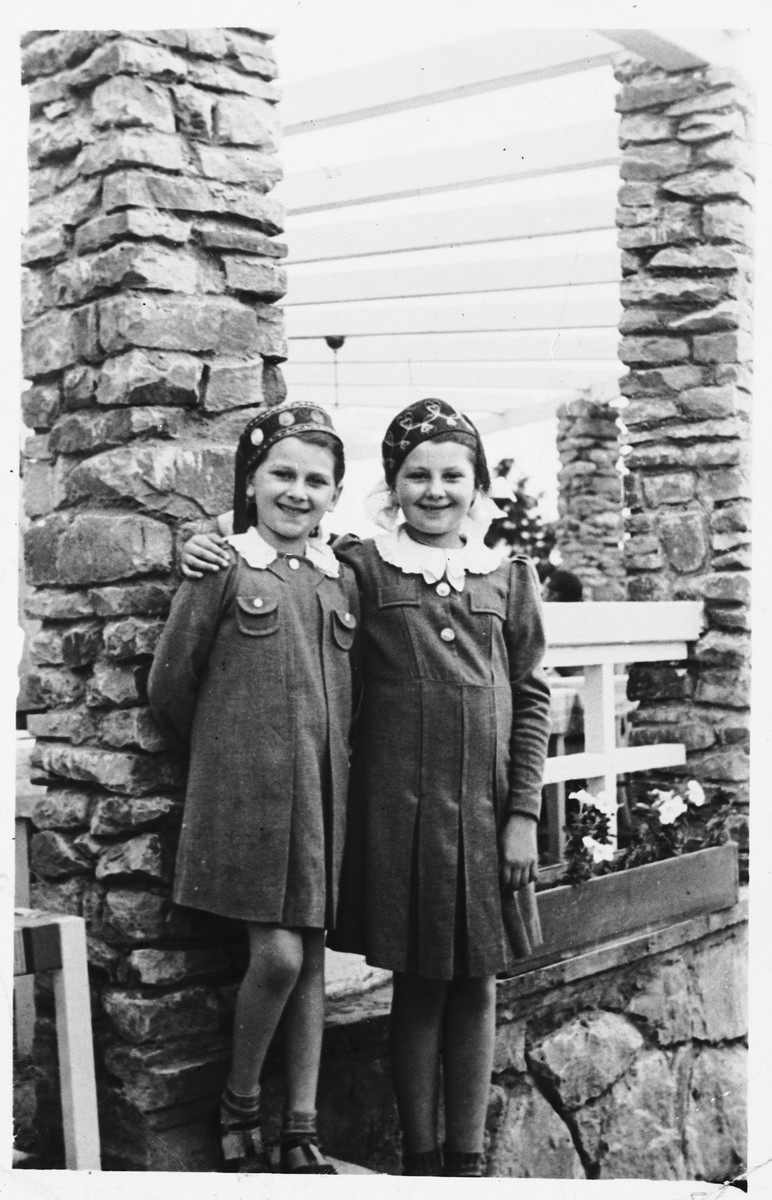 Two classmates from the Tarbut school in Luck stand outside a stone porch.  This photo was part of a going-away album presented to Sara Sztejnsznajd prior to her immigration to the United States.