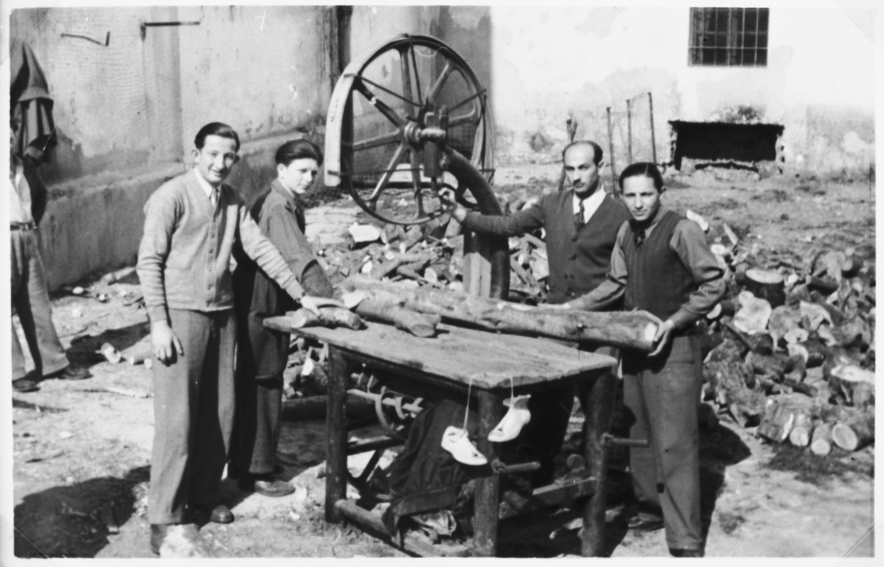 Four Jewish men cut lumber in the Cremona DP camp.  Shie Zoltak is standing second from the left.