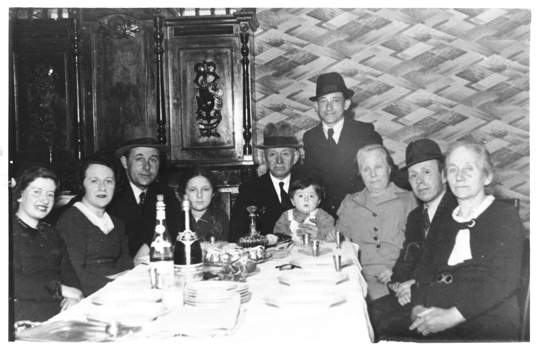 The Sztejnsznajd family celebrates its last seder in Luck prior to departing for America.  From right to left: a great-aunt, Avraham Gertner, Cipora Gertner, Yankel, Chaim Sztejnsznajd, Moshe Gertner, Sara Sztejnsznajd, Josef Sztejnsznajd, Goldie Sztejnsznajd, and a cousin also named Goldie.