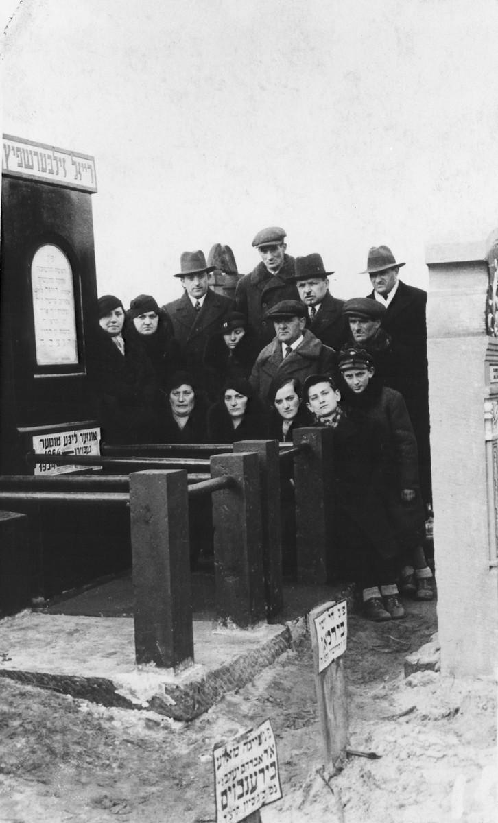 The family of Raizl Zilbersfietz gathers around her grave.