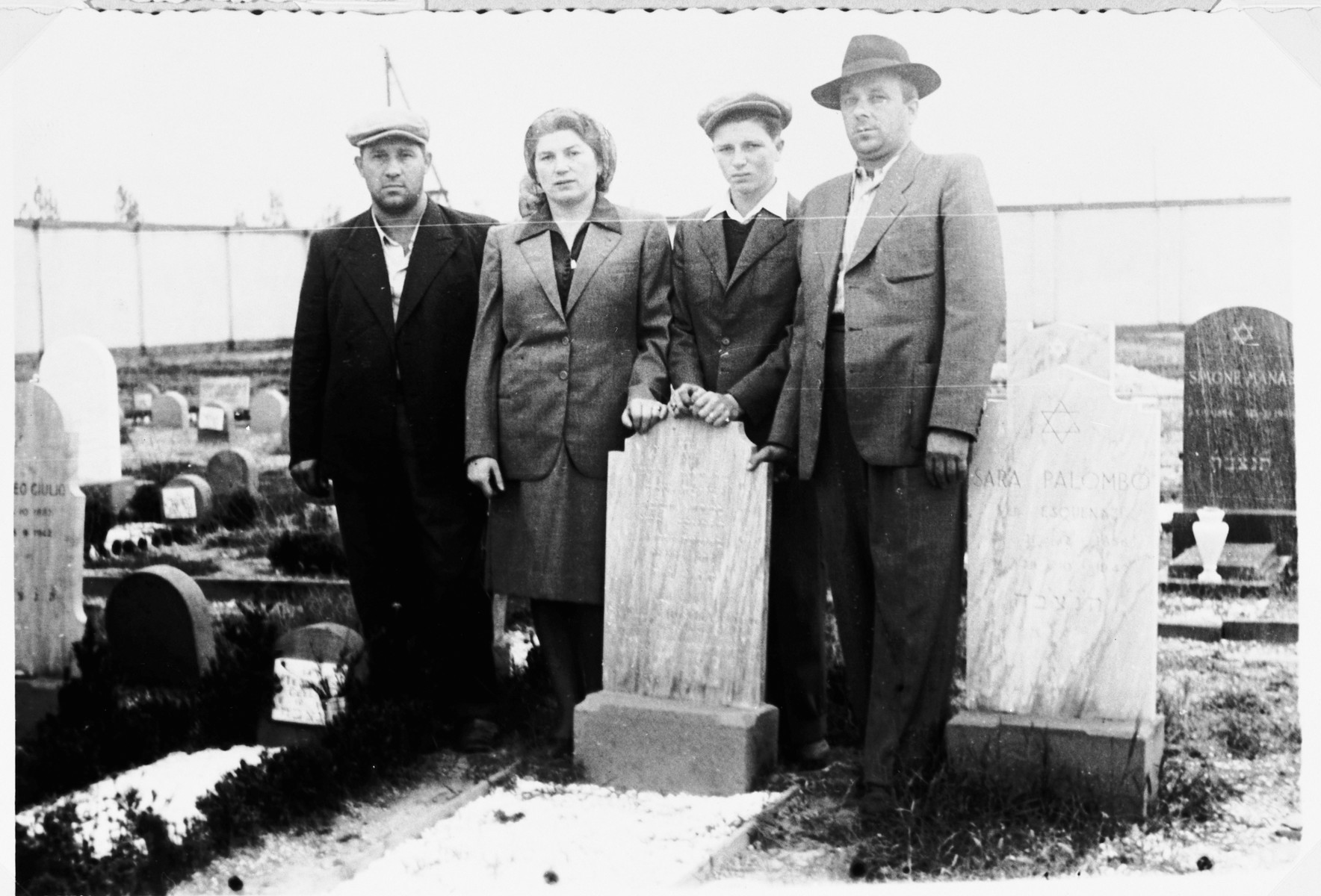 """Henia and Shie Zoltak pose next to the grave of their husband and father.  Two friends stand on either side.  On the left os Hersh-Leib Smobuk and on the right is """"Pelte""""."""