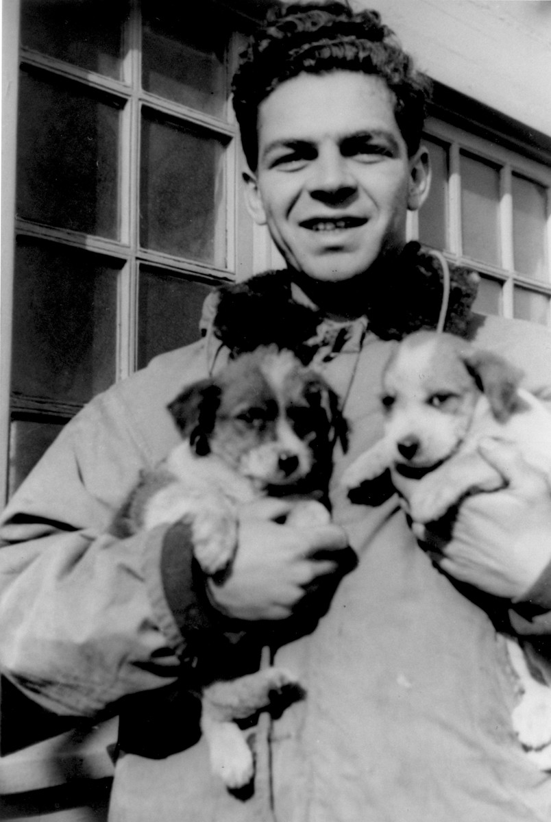 Avi Livney, a crew member of the President Warfield/Exodus 1947, poses on the deck of the ship with two puppies, the ship's mascots.