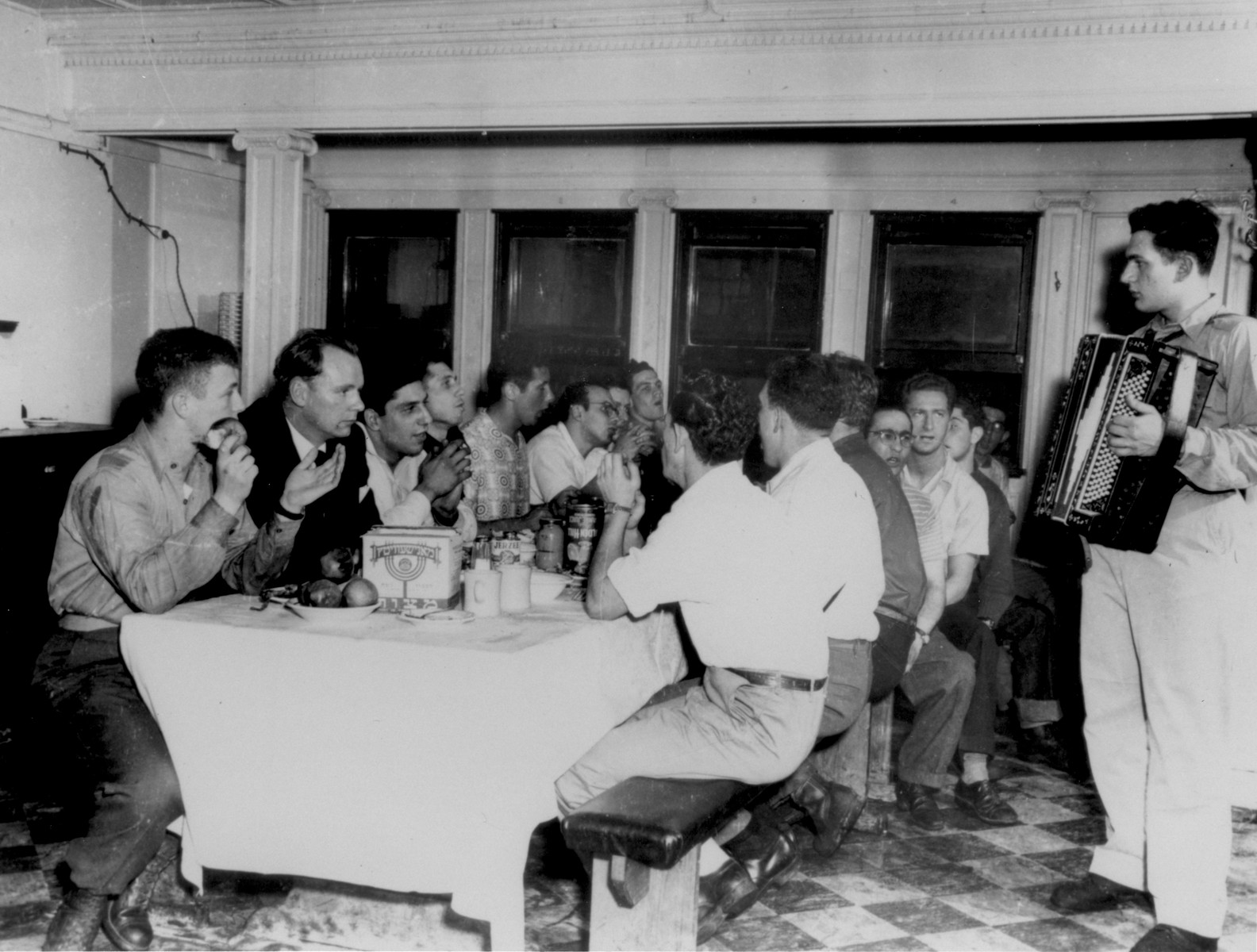 The crew of the Exodus 1947 attends a Passover seder in the ship's mess while en route from the United States to Europe.  The accordian player is William (Vevie) Siegel.  Pictured to the left of the accordian player are Al Naftel and Murray Aronoff.  On the left side of the table, the first four crew members from left to right are: Bentley Forman, John Grauel, Dov Mills and Avraham Siegel.
