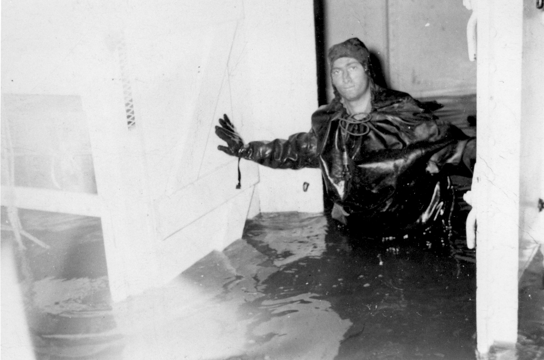 Murray Aronoff stands knee-deep in water in the engine room of the President Warfield after the gale that nearly sank the ship during its first attempt to cross the Atlantic Ocean.