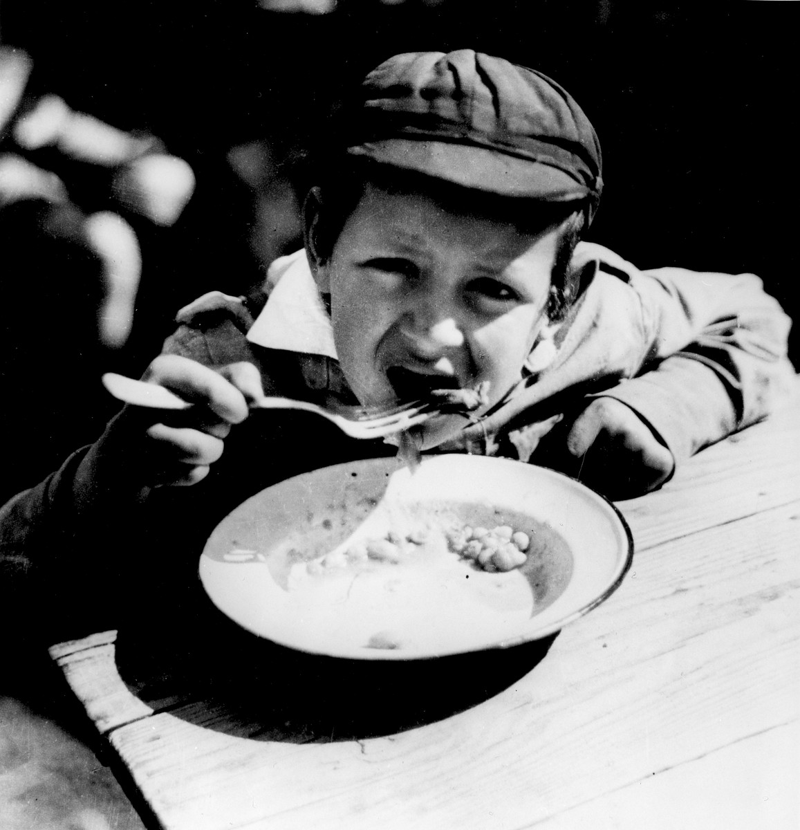 A child eats a meal in the TOZ summer home in Wisniowa Gora.    The TOZ (Society for the Safeguarding of the Health of the Jewish Population) is an affiliate of the international OSE/OZE organization. This summer home provided free housing, food, education, and physical activity for approximately forty impoverished boys, children of factory workers, for a period of three weeks.