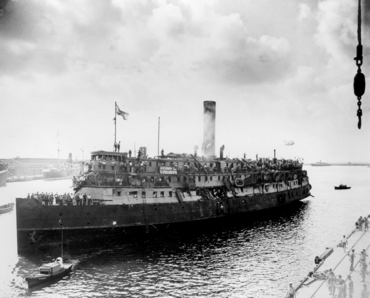 View of the damaged Exodus 1947 illegal immigrant ship as it is being towed into the port of Haifa, after its interception by the British navy.
