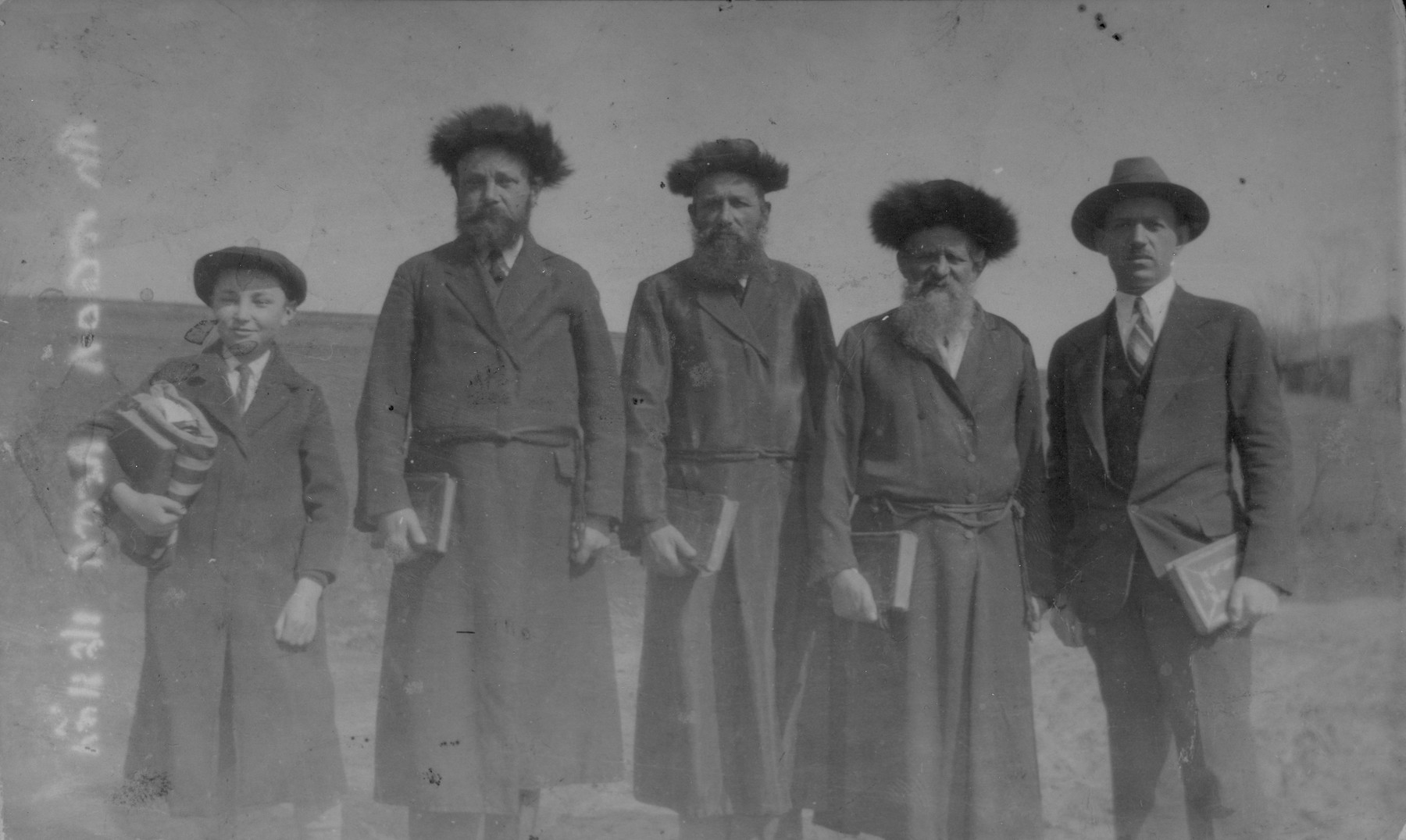 Group portrait of Hasidic Jews standing outside holding books in Raczyna, Poland.    Pictured from left to right are: Chaim Yankel Gurfein, Lejzer Gurfein, Moshe Yosl Dudlsack, Itzhak Dudlsack, and an unidentified American visitor.