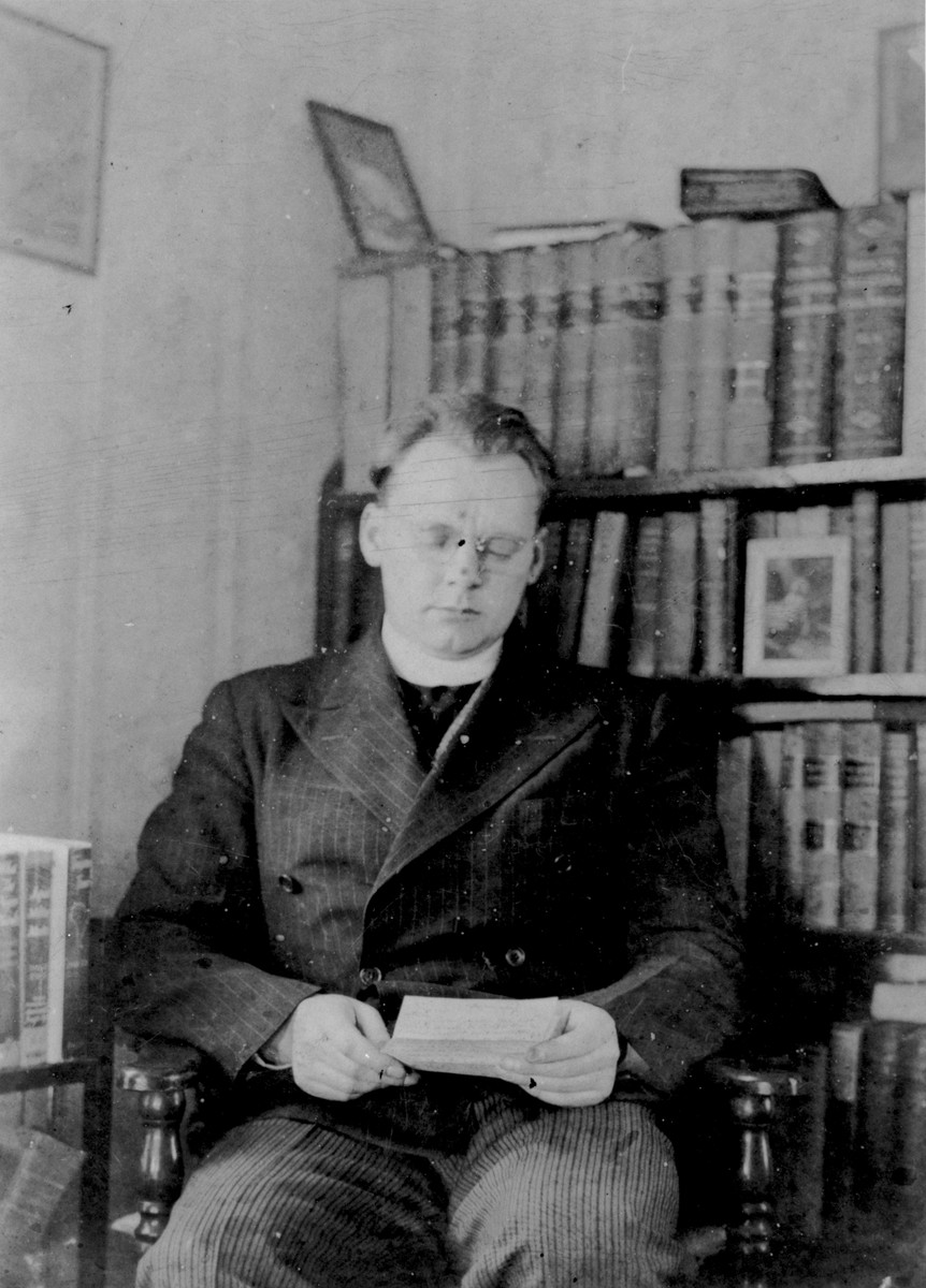John Stanley Grauel reads a letter in his study [in Maine].