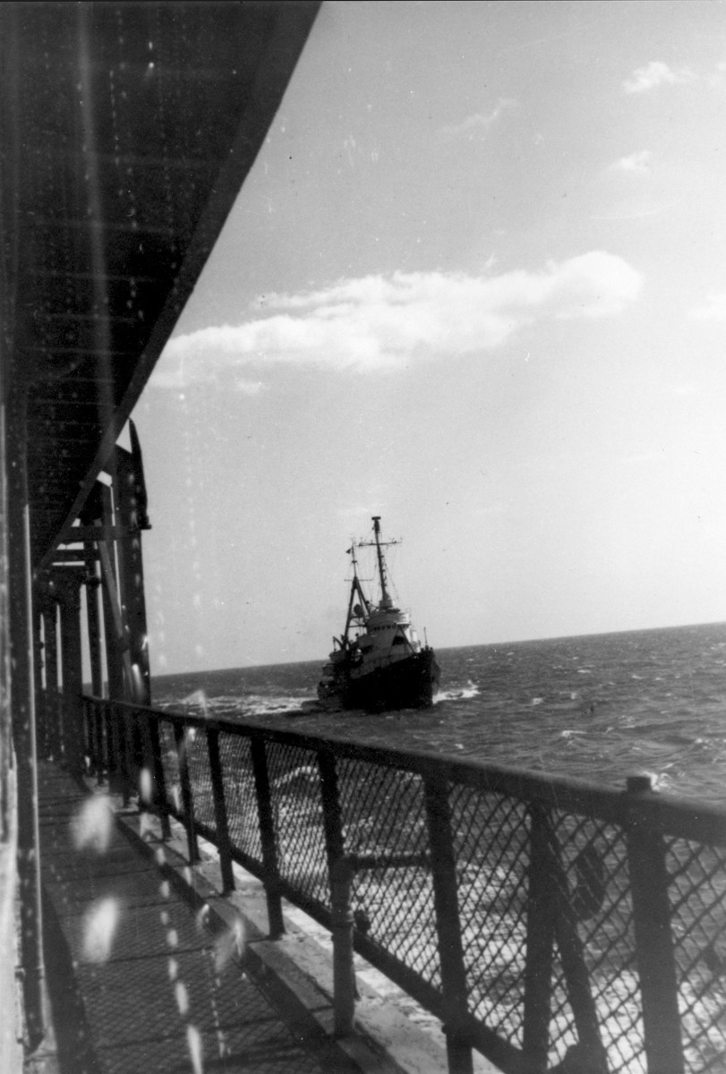 A US Coast Guard vessel escorts the President Warfield/Exodus 1947 ship into Norfolk harbor after it almost sank in a storm off Cape Hatteras during its first attempt to cross the Atlantic Ocean.