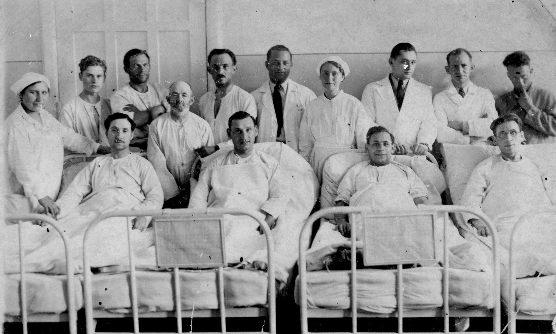 Doctors and nurses at the Jewish hospital in Biala Rawska pose with four of their patients who are lying in bed.