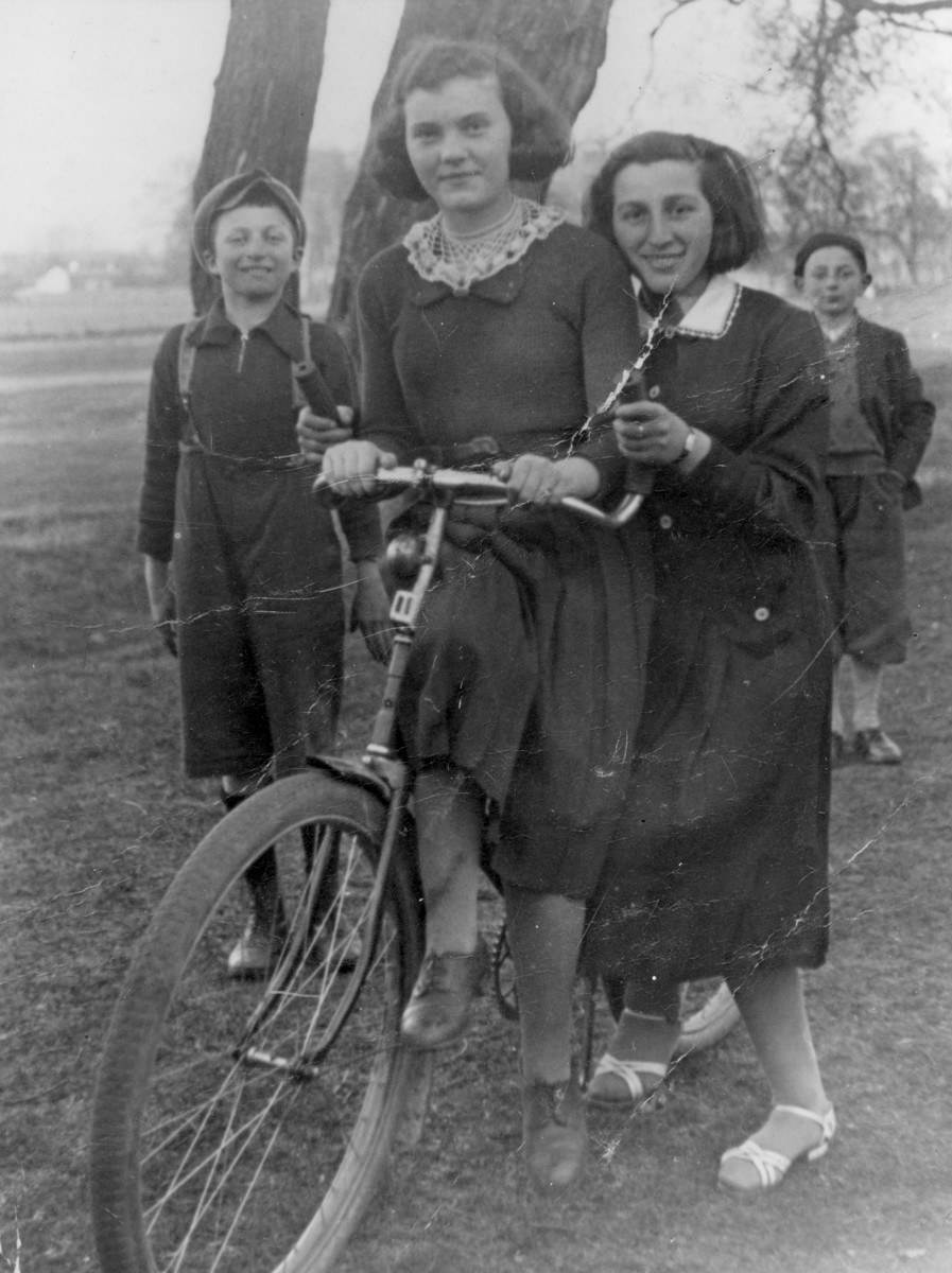 Two Jewish teenage girls pose on a bicycle while two younger boys look on at a vacation resort in Zarki.  Sitting on the bicycle is Rozka Zelcer; standing next to her is Rosenblum (first name unknown).  Both were friends of the donor, Jadzia Rottenberg (now Jeanette Ehrlich).