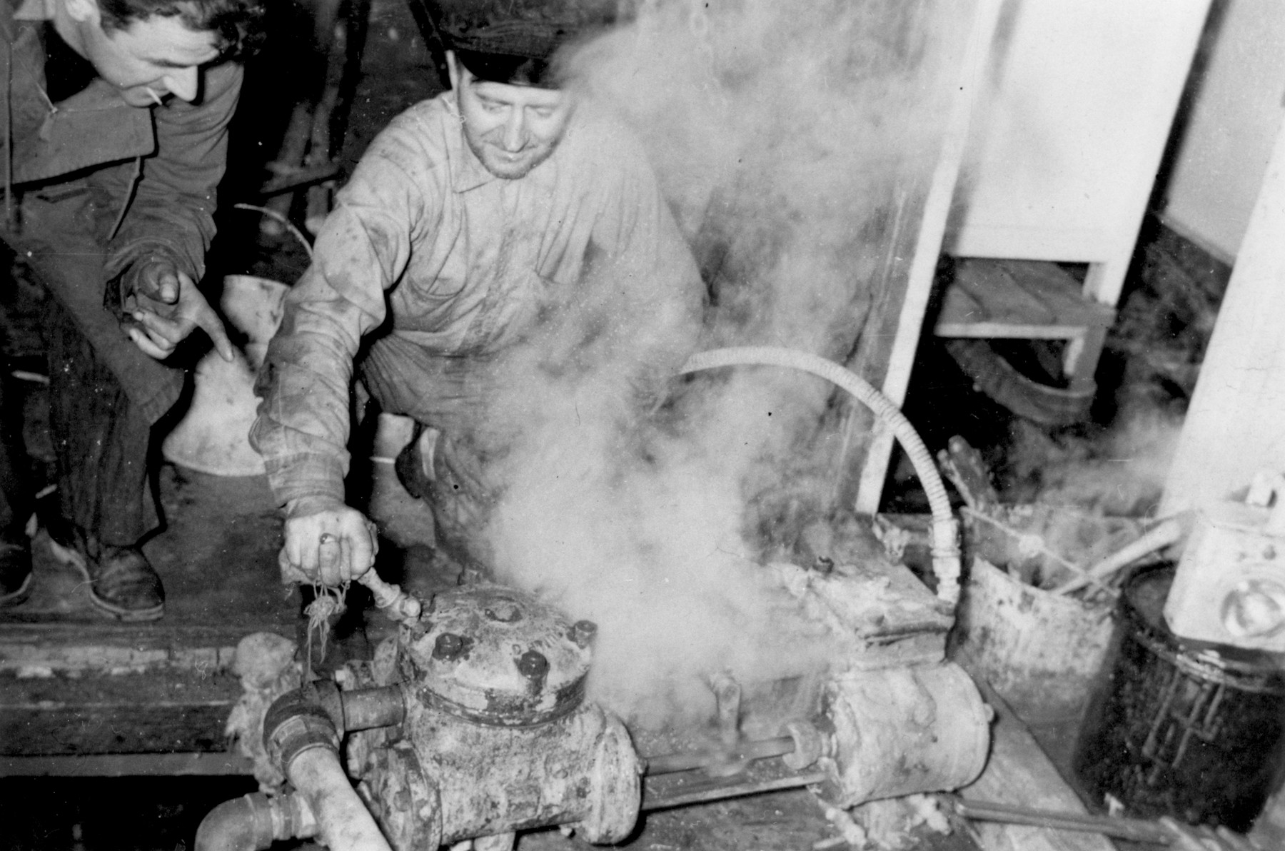 Engineer Frank Stanczak (right) and Michael Weiss attempt to keep the sump pump in operation in the engine room of the President Warfield after the gale that nearly sank the ship during its first attempt to cross the Atlantic Ocean.  The pump later exploded and several people were burned.