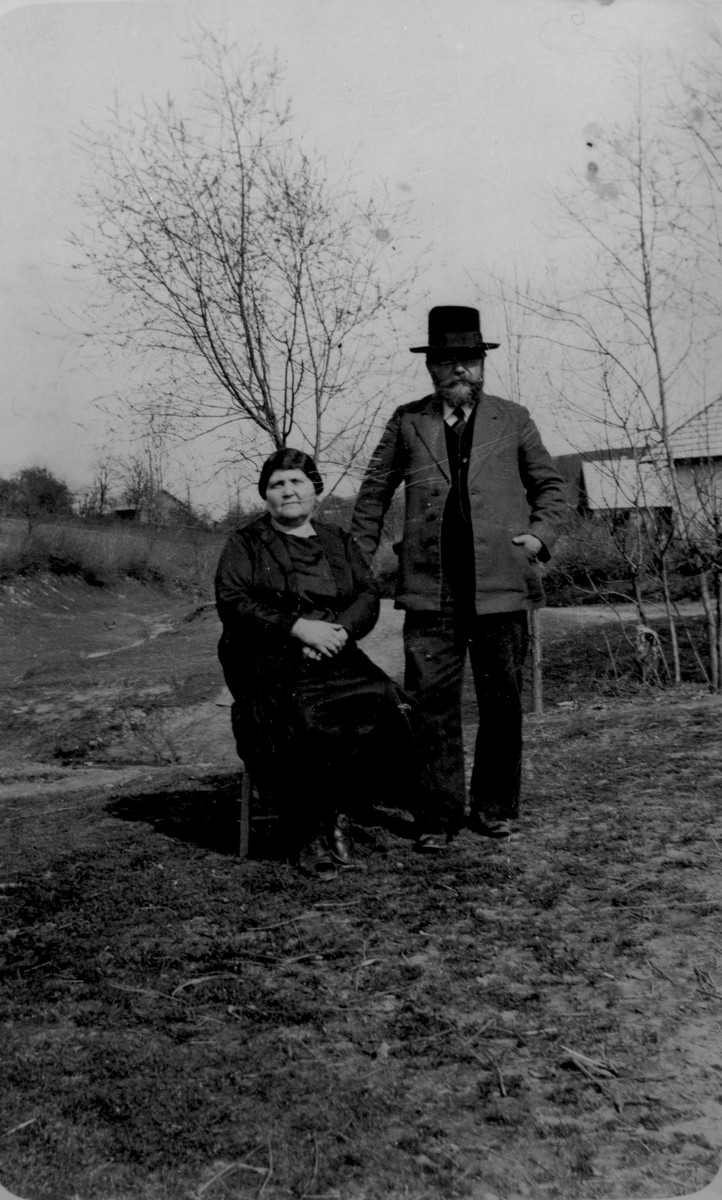 An elderly Jewish couple poses outside their home in Pruchnik, Poland.  Pictured are Lejzer and Chana (Taubenfeld) Gurfein.