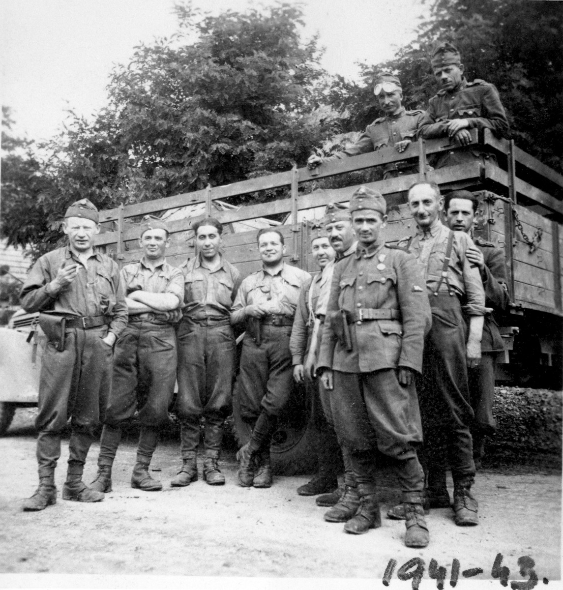 A unit of Hungarian soldiers that includes a Jew from Budapest, poses in front of a truck.  Among those pictured is Gyula Spitz (second from the left).