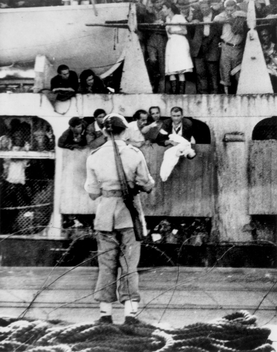 "The body of six-month-old Havivah Stein, who died of suffocation on board the illegal immigrant ship, the Jewish State, is held over the side of the vessel as it docked in Haifa after being intercepted by the British navy.    The passengers shout to the British personnel on the pier, ""You killed them!""  Tear gas was used to overcome resistance when the British boarded the ship."