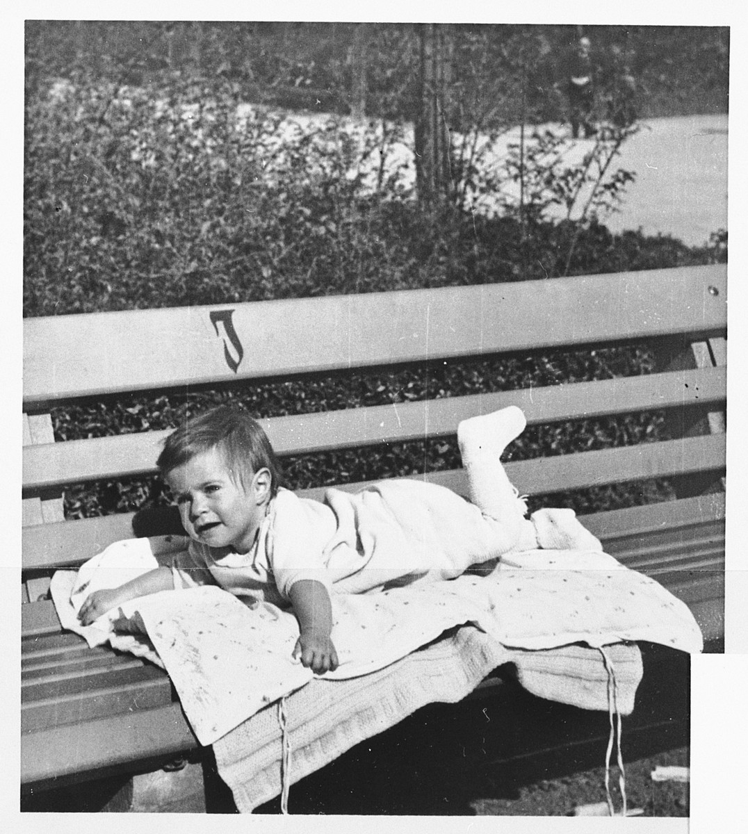A young baby lies on a park bench marked with a J to indicate it is only for Jews.  Pictured is Marianne Harpuder (now Price).