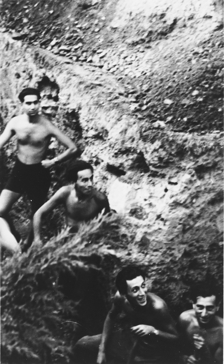 Four Slovak Jews pose on a stony hill in the Zilina labor camp.  Fritz Bruck is standing at the top left.  Kiki Danzig is in the center.  Max Stern is at the lower left.  The photograph was taken by Manfred Hirsch, a German friend who had come to visit.