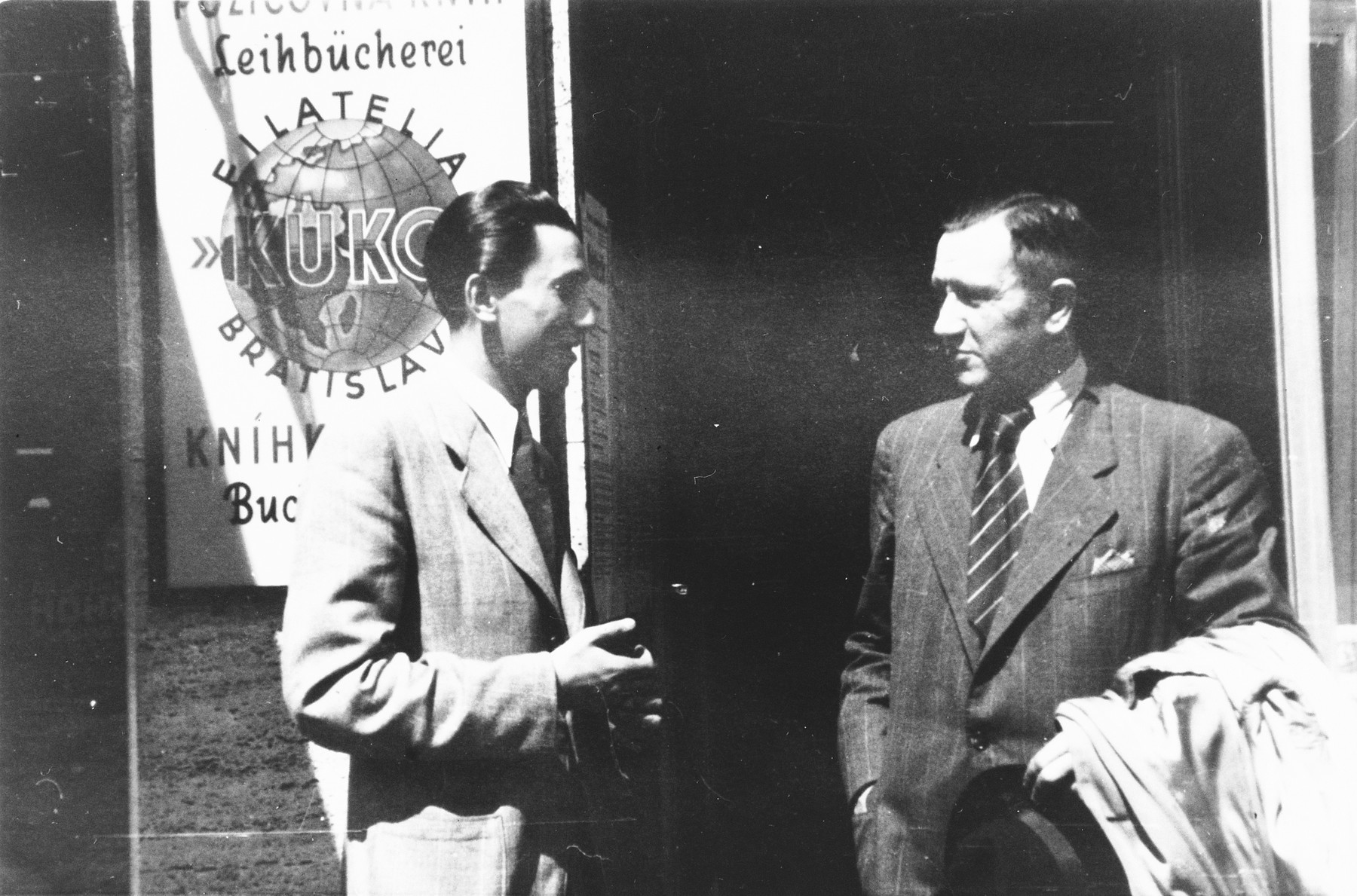 Max Stern talks to a friend outside his stamp store, Filatelia Kuko.