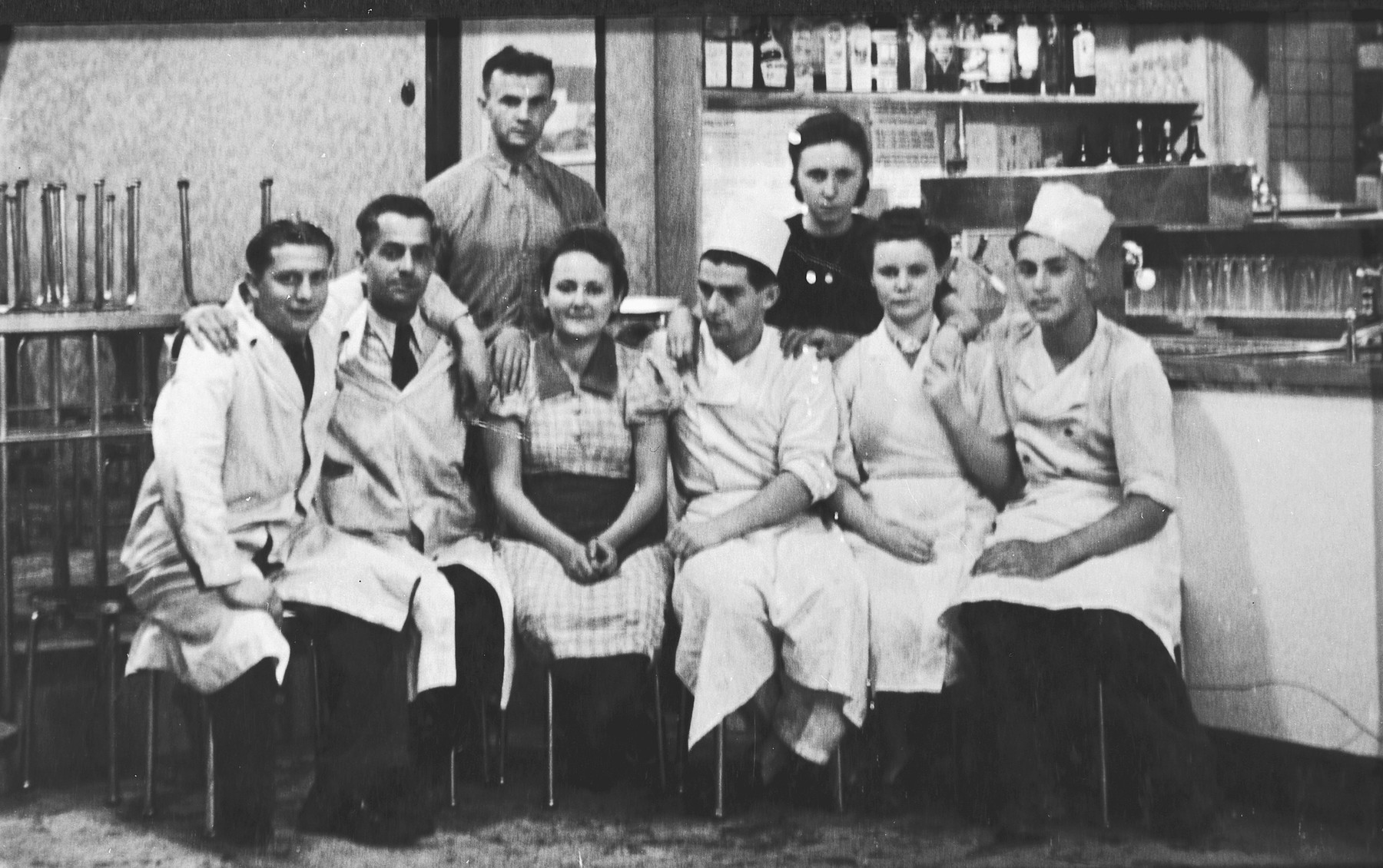 Group portrait of cooks in a dining hall or kitchen in Prague during the Nazi occupation.  Among those pictured is Edgar Krasa (left), who was working as an apprentice chef.