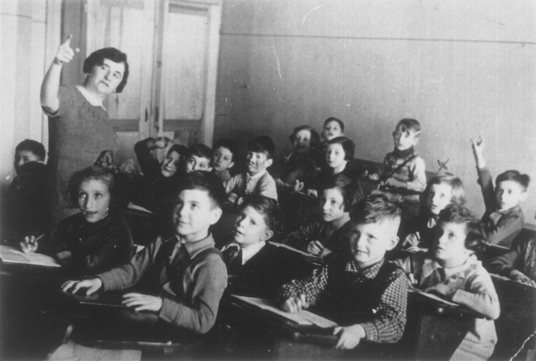 Students sit at their desks in a first grade classroom in Berlin.  Hannelore Mansbacher is sitting on the right side in front of the child who is holding up his hand. The teacher, Hilde Goldschmitt, later emigrated to Israel.