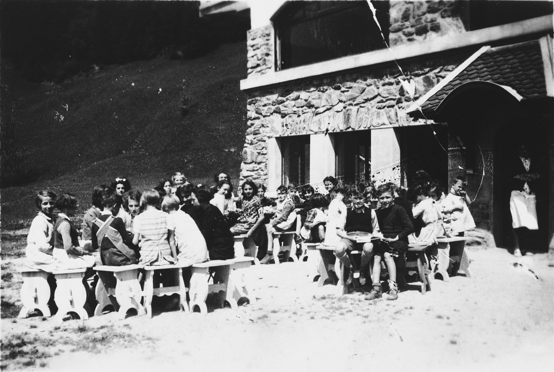 Children sit on outdoor benches in a Secours Suisse home in Praz sur Arly.