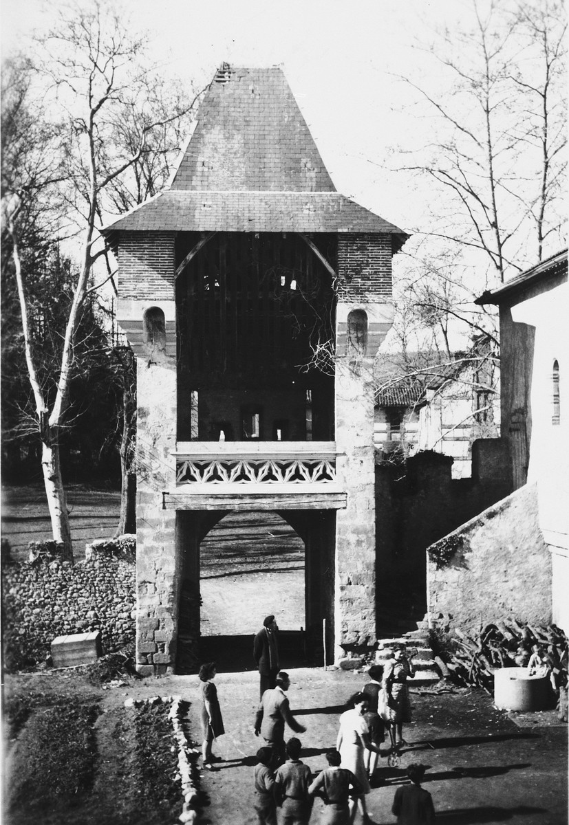 People gather in the courtyard garden near the entry tower of Chateau La Hille.
