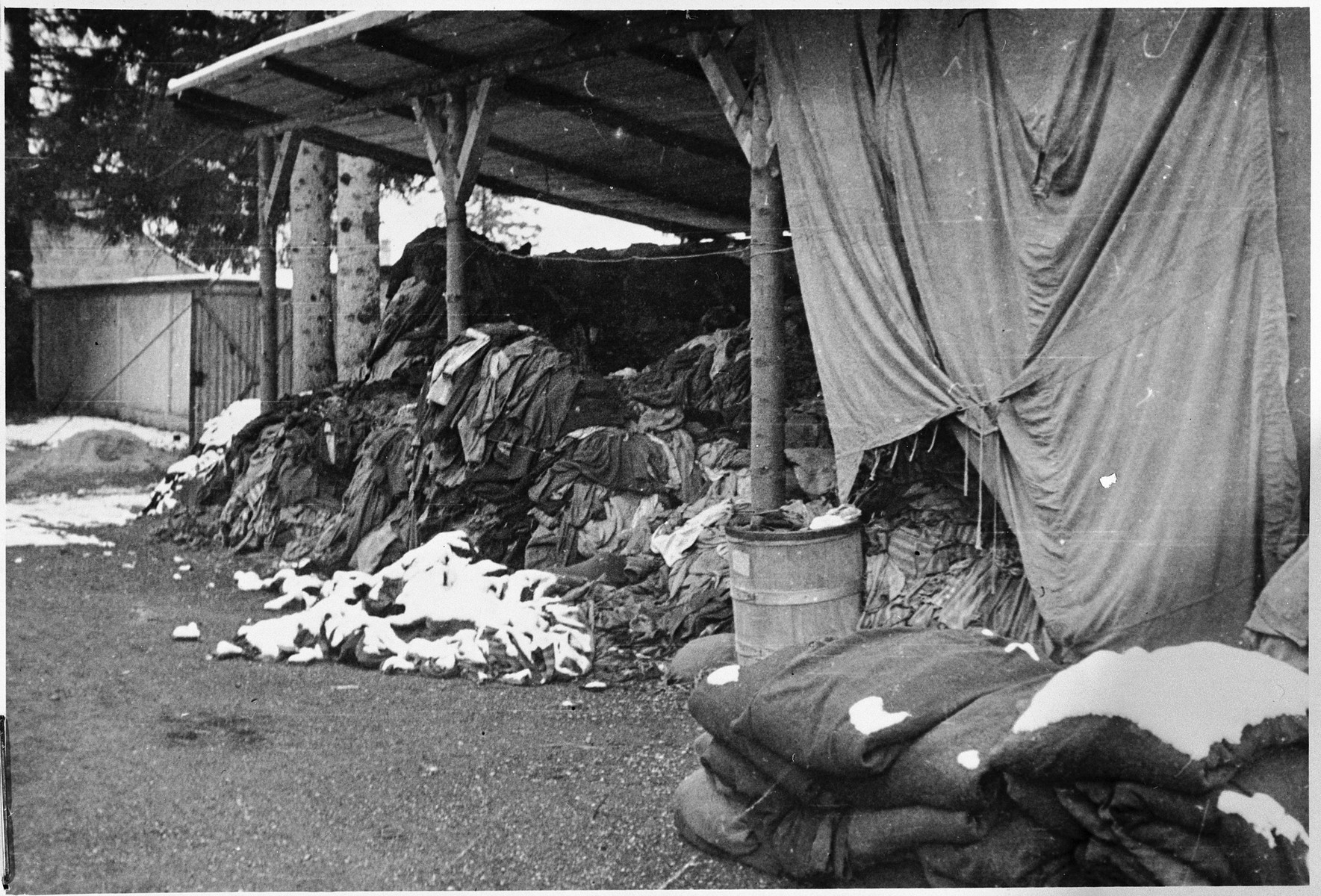 View of clothing piled in an open shed in the Dachau concentration camp.