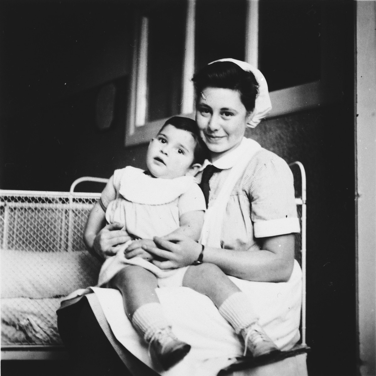 A Jewish refugee youth cares for a young child while training to become a pediatric nurse in Switzerland.  Pictured is Ilse Wulff (right).