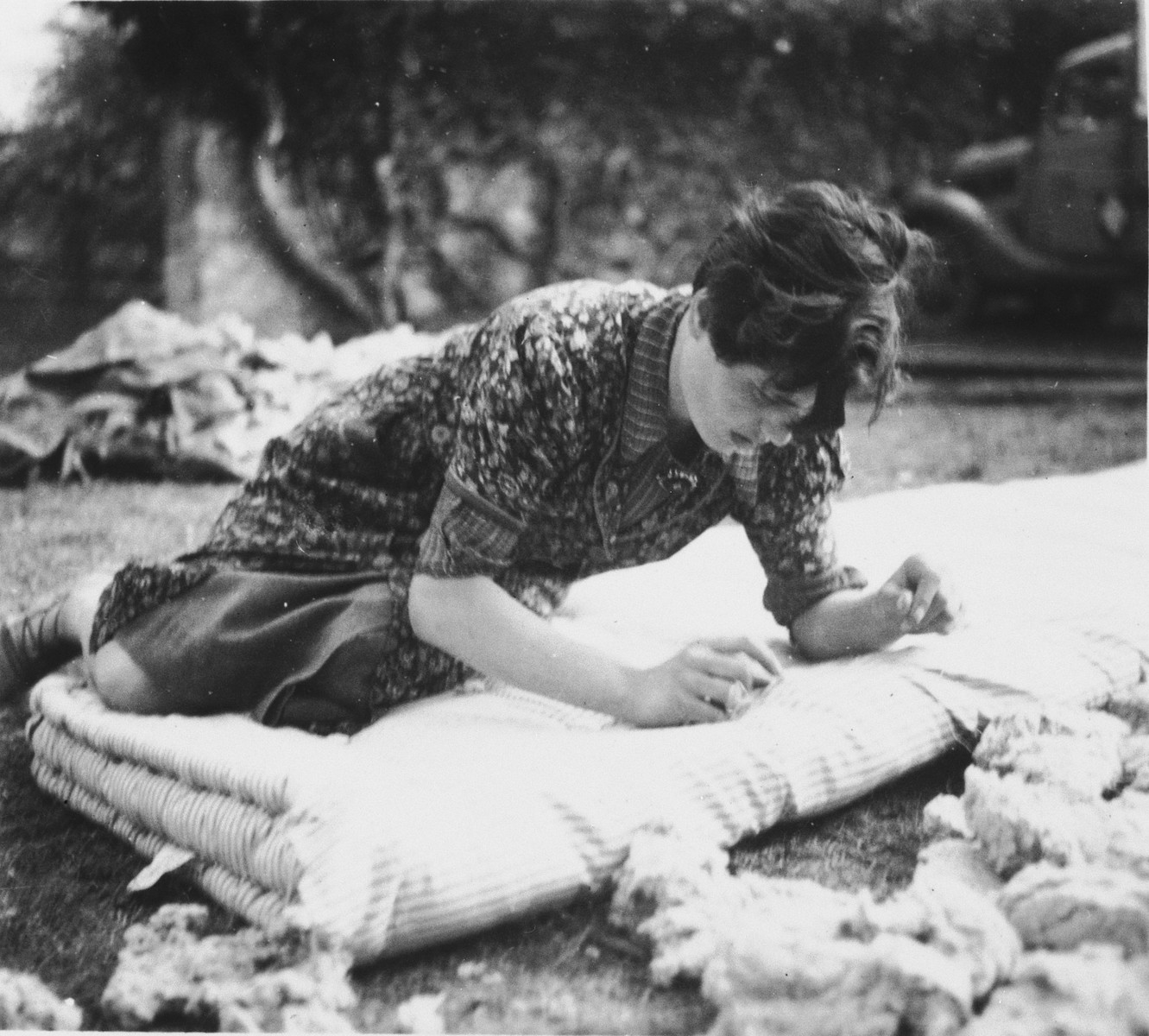 Ruth Herz darns a feather mattress in the Chateau La Hille children's home.