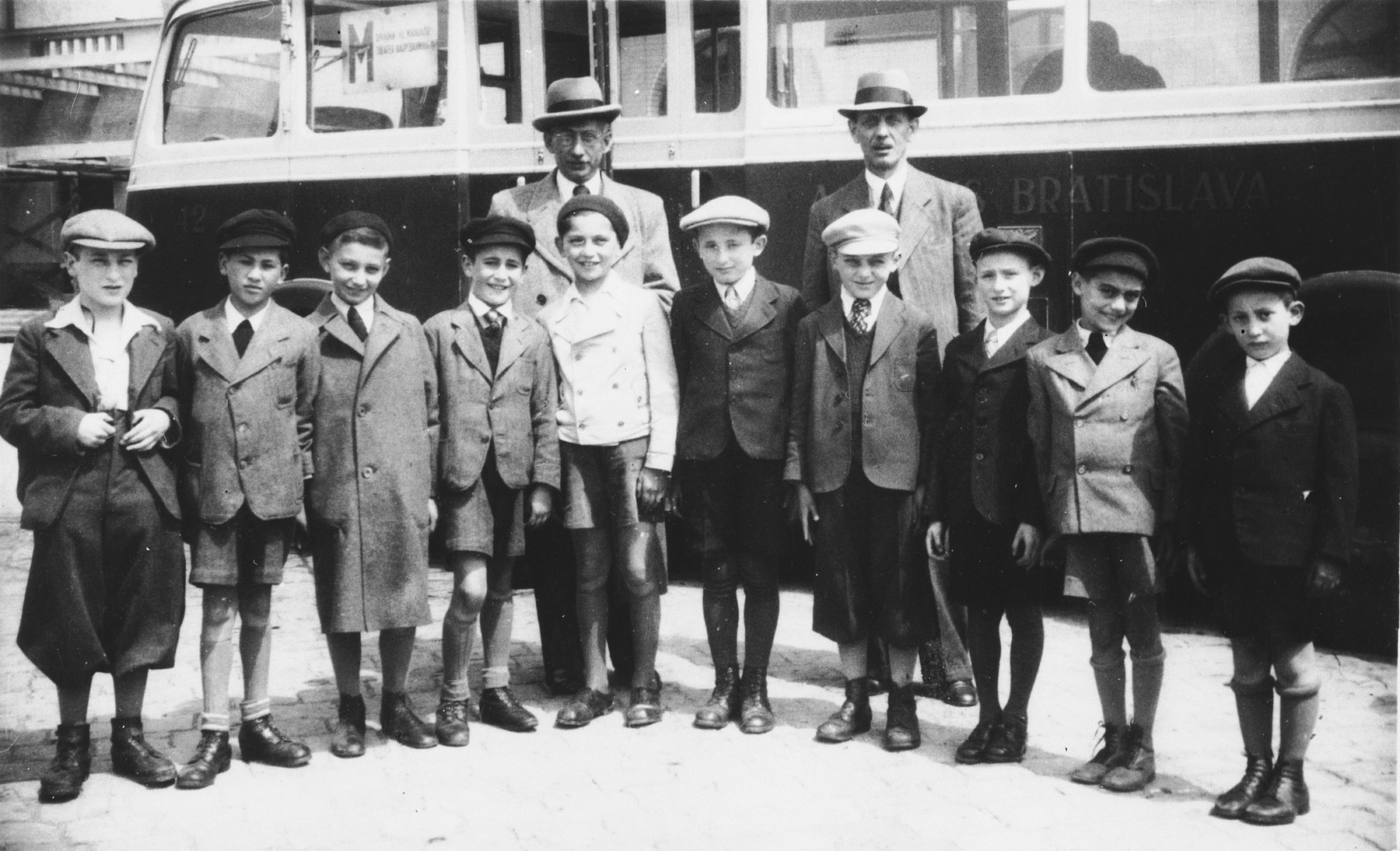 A group of boys from Bratislava prepares to leave for England on a Kindertransport.  Those pictured include Kurt Stern (second from left), Harry Stern (fourth from left).  Standing in the back are Mr. Turk on the left and Moses Stern on the right.
