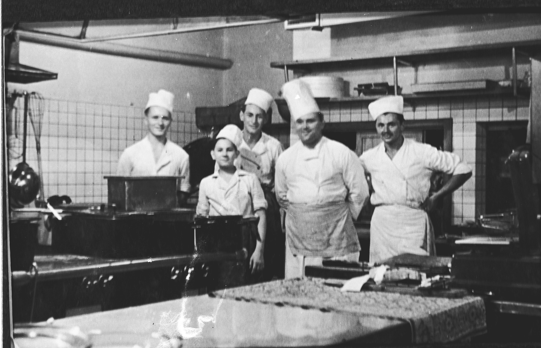 Group portrait of cooks in a kitchen in Prague during the Nazi occupation.  Among those pictured is Edgar Krasa, who was working as an apprentice chef.