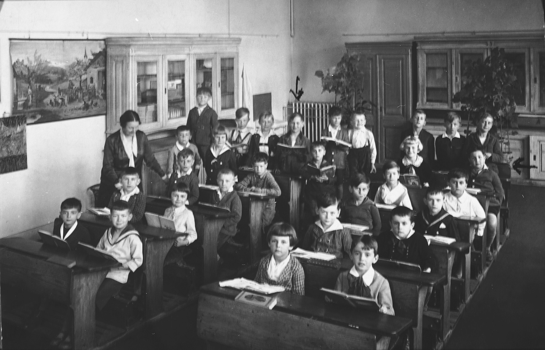 Pupils in the first grade sit in their classroom at a public school in Prague.  Among the students are several Jewish children.  Among those pictured are Edgar Krasa (back row, left) and Max Widder (second to last row, right side).
