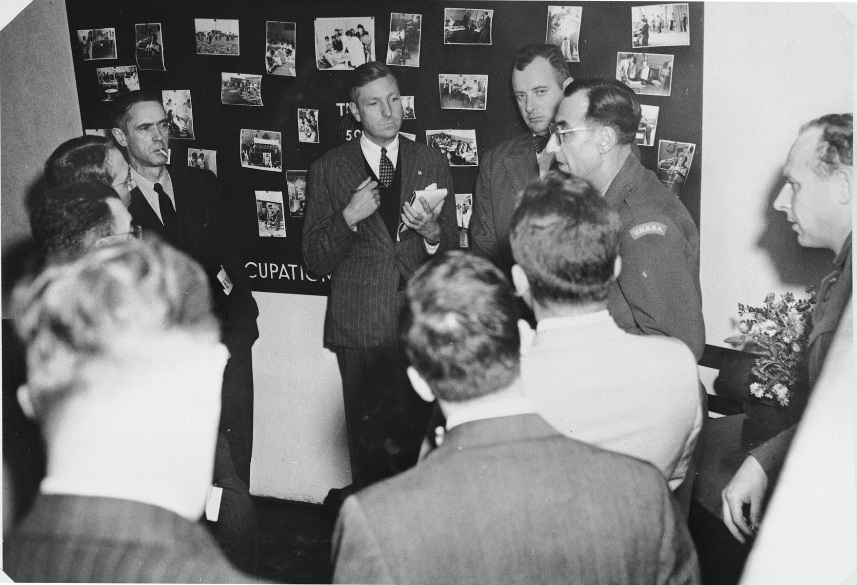 "American editors and newsmen talk with camp officials in front of a photo display during a tour of the Zeilsheim displaced persons camp.  The original caption reads, ""While making an extensive tour of the military government installations and activities in the U.S. army occupational forces, American newsmen and editors visited the Zeilsheim DP camp in Hanau, Germany.  In this picture, the American newsmen are shown as they converse with the head of the union at Zeilsheim, Mr. Zylbertal."""