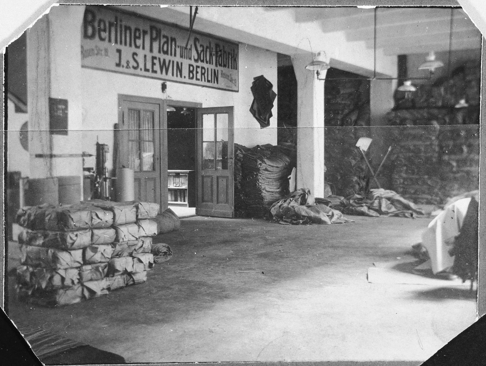 Storeroom with stacked bundles inside J.and S. Lewin's tarpaulin and sack factory.