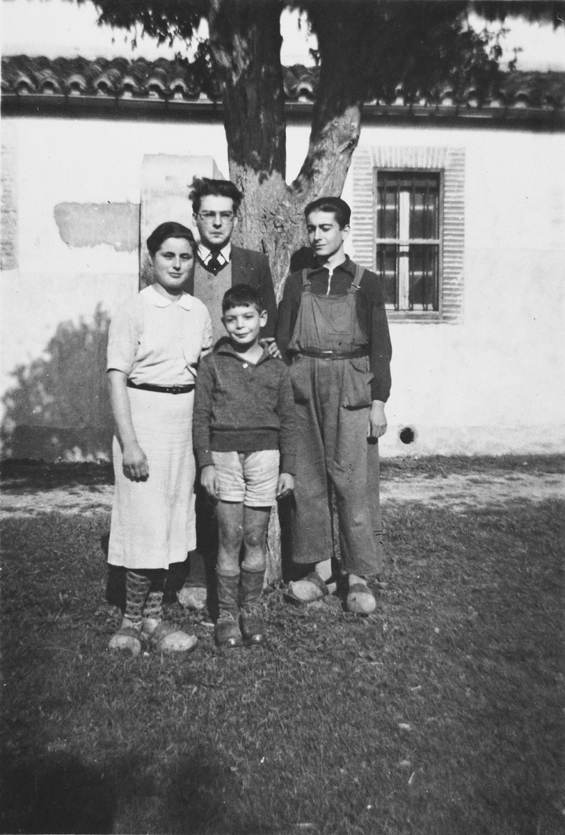 Four children stand under a tree outside the children's home in Seyre.  Ruth Herz is on the left.  Walter Kamlet is in the back.  Rolf Weinmann is in front and Werner Rindberg is on the right.