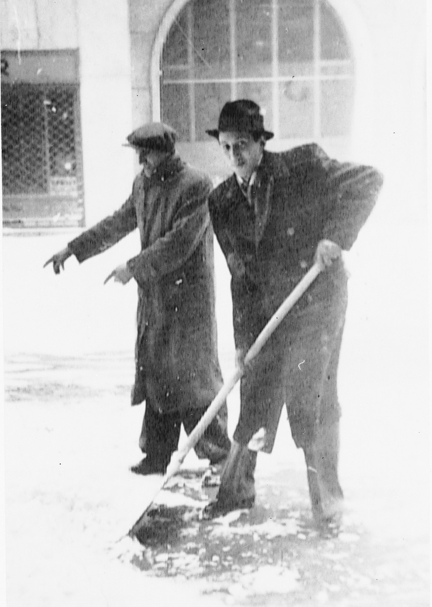 Max Stern is forced to shovel snow under the direction of a Slovak guard.  The photograph was taken by a German friend, Manfred Hirsch.
