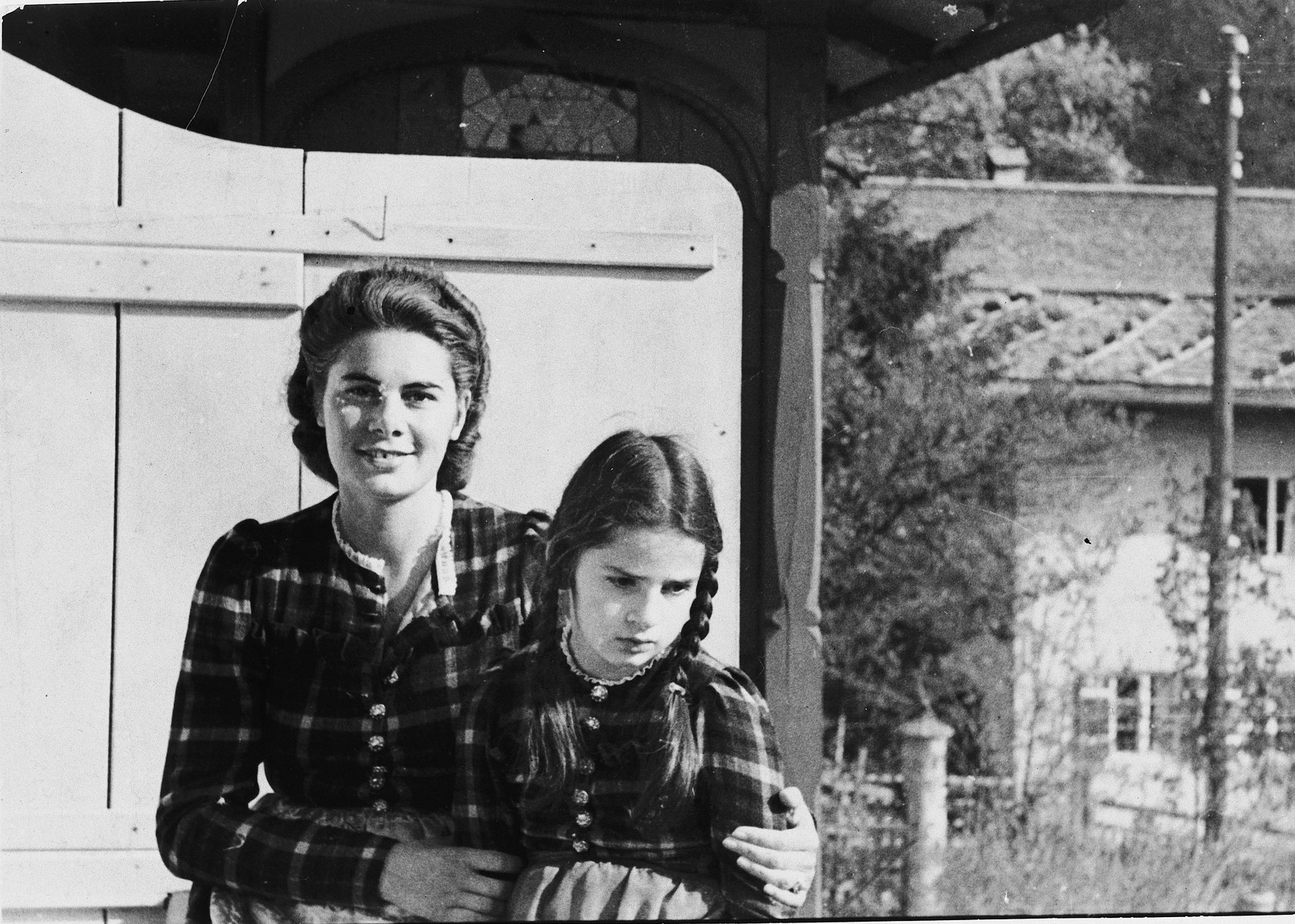 A mother and daughter of mixed German-Jewish origins pose in front of a wooden gate in Garmisch-Partenkirchen.  Pictured are Inge and Sylvia Glaser.